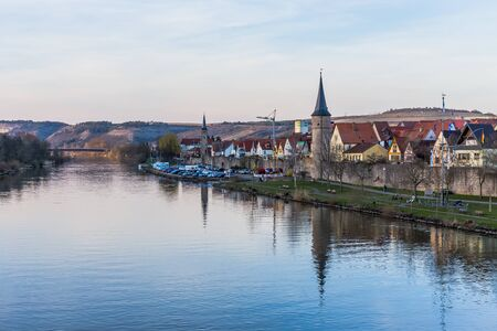 river main: Franconian City of Karlstadt at the River Main in Germany. Lovely evening with clear blue sky in early April spring. Old medieval city with city wall and tower Stock Photo
