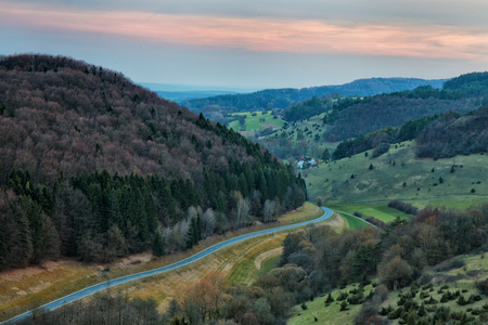 motorcycling: Springtime in Franconia, Germany. Landscape Image of a Hill Landscape near Rosdach with a beautiful country road in the evening, popular for motorcycling Stock Photo