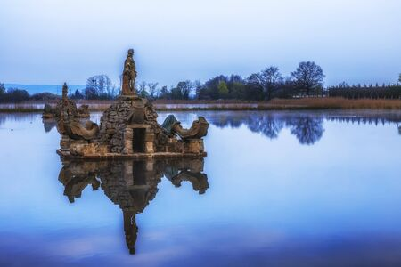 mirror image: Old Fountain in a lake in Bavaria. Mirror Image. HDR technique Stock Photo