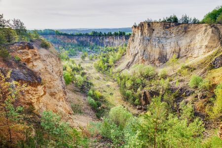 landscape format: Franconian Canyon. Retired Quary in Germany, Europe. Taken on a warm spring morning. Green trees and orange stone rocks. Panorama Landscape Format