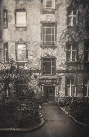 frontal view: Berlin Apartment House. Reduced Sharpness and Area Tilt Shift Focus and Low Contrast Black and White Sepia for nostalgic Vintage Retro Look. Frontal View. Dilapidated Facade. City House in Germany Stock Photo