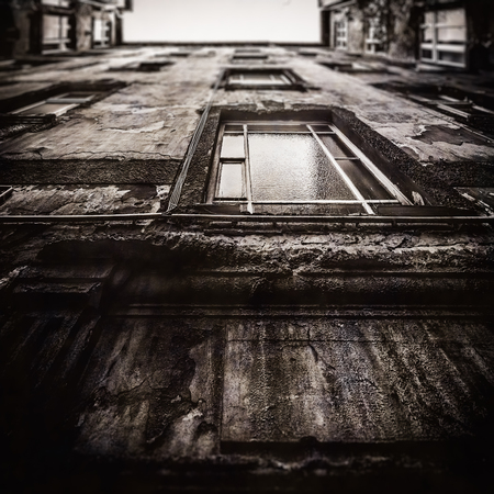 tilt view: Berlin Apartment House. Reduced Sharpness and Area Tilt Shift Focus and Low Contrast Black and White Sepia for nostalgic Vintage Retro Look. Upwards View. Dilapidated Facade. City House in Germany