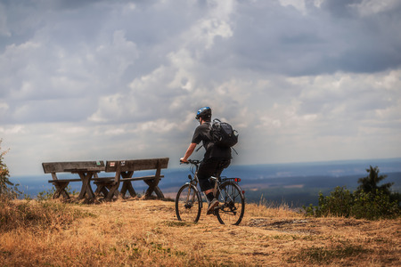 mountainbiking: Biking in the Franconian Hills in Northern Bavaria. Caucasian Young man in black sports outfit with his Trekking bike on a rock, looking into the distance. Shot in High Summer August on an afternoon