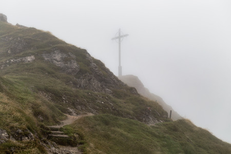 bleak: Karwendel Mountain Range in Tyrol, Austria on a foggy and rainy day in August. High Mountains landscape in a bleak and desolate landscape. Cross on the Summit of the Seefeld mountain range