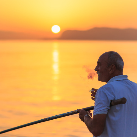 italian man: PALERMO, ITALY - SEPTEMBER 19 2015: Italian man with white shirt and white hair fishing in the sunrise on Sicily, Italy