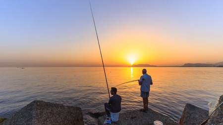 ocean fishing: PALERMO, ITALY - SEPTEMBER 19 2015: Young and older italien men fishing in the sunrise on Sicily