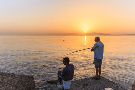 italien: PALERMO, ITALY - SEPTEMBER 19 2015: Young and older italien men fishing in the sunrise on Sicily