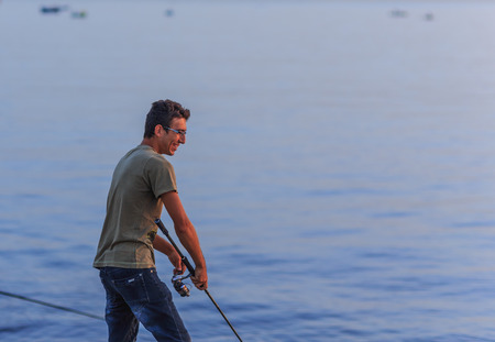italian man: PALERMO, ITALY - SEPTEMBER 19 2015: Young smiling italian man fishing in the sunrise at Sicily