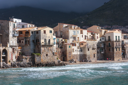 mediterranean houses: CEFALU, ITALY - SEPTEMBER 20 2015: Coastal Town and Tourist Location Cefalu at the sea of the island of sicily. Warm summer day with mediterranean houses at the beach Editorial