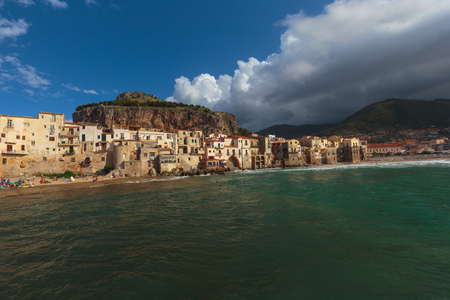 mediterranean houses: CEFALU, ITALY - SEPTEMBER 20 2015: Coastal Town and Tourist Location Cefalu at the sea of the island of sicily. Warm summer day with mediterranean houses at the beach Stock Photo