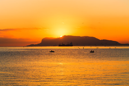 With Love from Sicily. Dramatic Sunrise over the Mediterranean Sea. Romantic Dawn from Palermo, Italy on the island of sicily. Picturesque warm colors and silhouettes of fishing boats in the morning