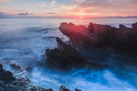 mondello: Sunrise over the Coast of Sicily. Dawn at Capo Gallo Coast near Palermo at Mondello on a warm autumn morning. Lovely sun and waves in the sea