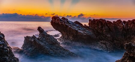 Mornig Coast Sunrise on Island Sicily in Italy, Europe with sunrays and clouds. Amazing landscape and water