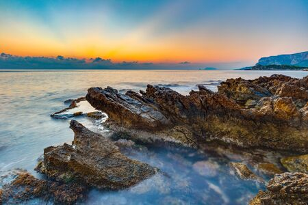 gallo: Mornig Coast Sunrise on Island Sicily in Italy, Europe with sunrays and clouds. Amazing landscape and water