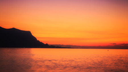 Strong Orange Sunset behind a hill at the coast of Sicily Standard-Bild