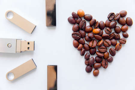 USB stick and heart from coffee beans on white background.
