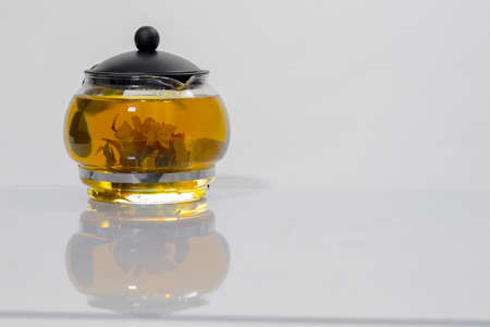 Green Chinese tea flower bud blooming in glass teapot. Stock Photo