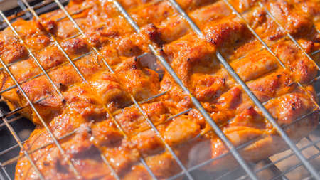 the chicken is fried on the grill grate on the grill.