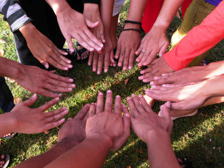 A GROUP OF HANDS FORM CIRCLE photo