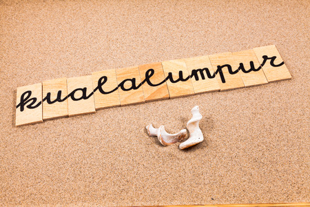 season s greeting: Words FORMED from small pieces of wood container containing a sun and beach tourist destination Kualalumpur Stock Photo