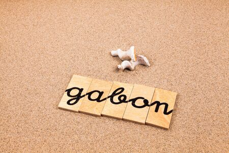 appoints: Words FORMED from small pieces of wood container containing a sun and beach tourist destination Gabon