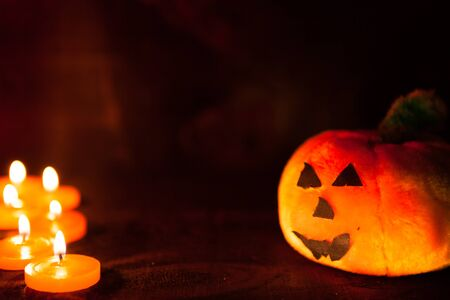 iluminated: Halloween picture with the face of a pumpkin on wooden background Stock Photo