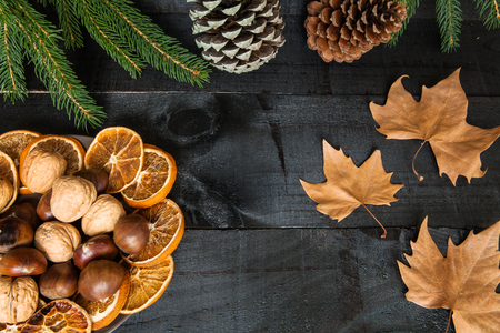 dinners: Composition of cutlery on wood background for a decorative dry branches and oranges, fruit and leafs pain for casual dinners or family celebrations in autumn winter season