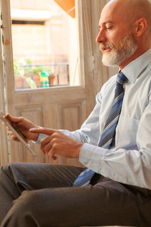 homeoffice: Businessman middle-aged bearded and suit jacket on a tablet searching on blurred background Stock Photo