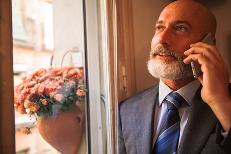 homeoffice: Businessman middle-aged bearded and suit jacket With His mobile internet surfing device Stock Photo