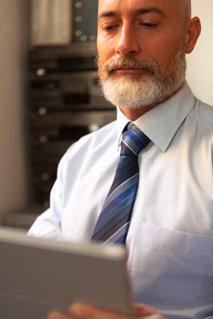 homeoffice: Businessman middle-aged bearded searching and suit jacket on tablet