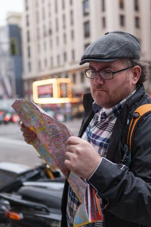 internet explorer: Traveler Young man with glasses and a hat looking for a place in a map,