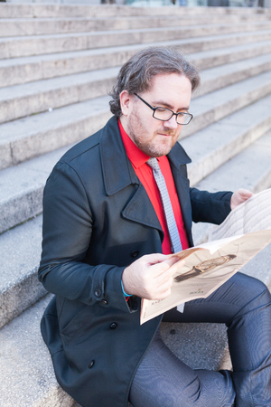 average guy: A young businessman reading a newspaper with glasses is thinking in urban scene