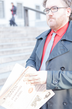 average guy: A young businessman with a newspaper with glasses is thinking in urban scene, the picture has-been shooted in high key