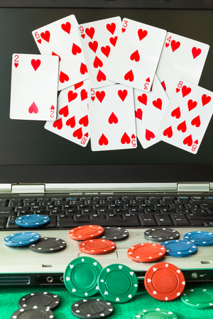 money risk: Poker chips and cards on a laptop. Image related to classic and online casino games on a wood background from a players perspective