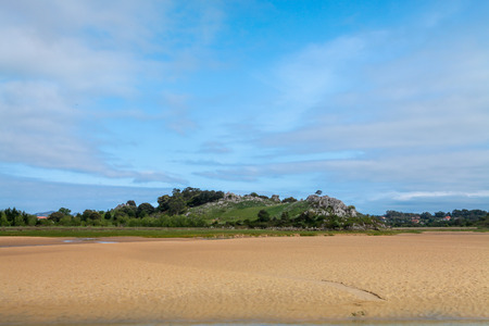 characterized: Marsh island village in Cantabria. The image Represents the marsh island village in Cantabria, Spain at low tide, the landscape is Characterized by the contrast of green and white sand