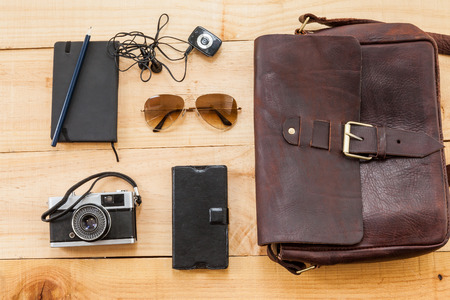 book bag: Hipster stuff bag.The retro image shows a hipster or bag for man or woman with glasses Such stuff as, vintage camera, leather book bag and a note on a wooden background