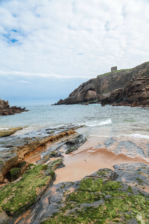 cantabrian: Santa Justa Beach in Tagle, Cantabria, Spain. The picture dealer to a landscape of the Cantabrian coast, the beach of Santa Justa in Tagle, sea, rocks, a cloudy sky and the chapel With its bell tower in the background