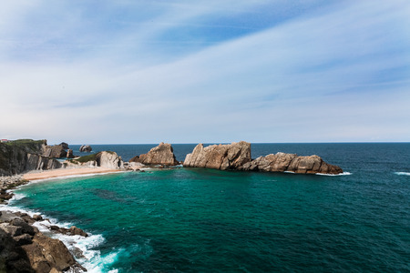 cantabrian: The picture dealer to a landscape of the Cantabrian coast, beach Arnia in Liencres. The sea, blue cloudy sky and an open rockface. Stock Photo