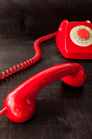 thereof: The retro red telephone. The image above dealer in vintage red phone on a dark wood background Conceptualizing communication or lack thereof Stock Photo