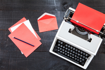 telecommute: Red typewriter. The image above dealer to retro typewriter and some colored paper on a dark wood background with a rede color paper Conceptualizing esta like danger, love or something different Stock Photo