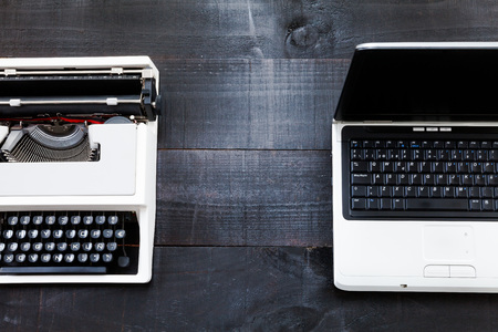 Typewriter and laptop. The image above dealer to retro typewriter and a laptop on a dark wood background Conceptualizing That the time of technology is getting older the picture is taken from a top view