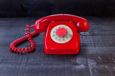 The retro red telephone. The image above dealer in vintage red phone on a dark wood background Conceptualizing communication or lack thereof Stock Photo