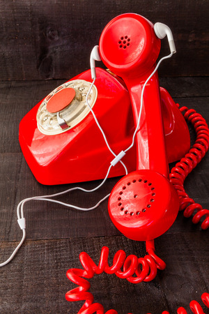 The retro red telephone. The image above dealer in vintage red phone on a dark wood background Conceptualizing communication or lack thereof wearing earphones