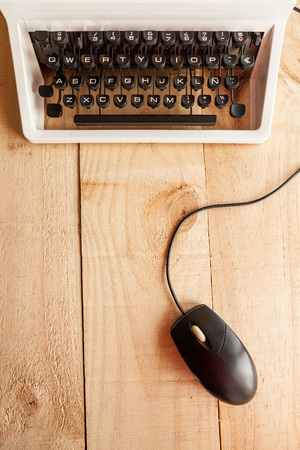 obsolescence: The image shows an antique typewriter to a computer mouse connected to laptop and Conceptualizing imitating the obsolescence of technology