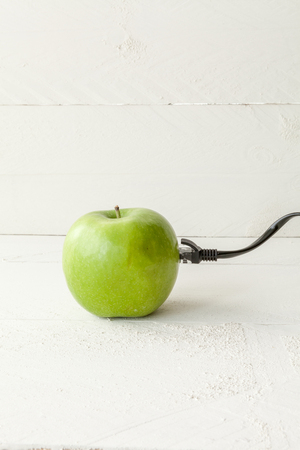 ethernet cable: The picture shows an apple connected to an ethernet cable conceptualizing the internet of things and wearables
