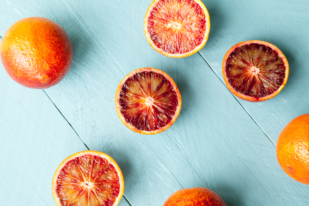 sanguine: Sanguine and whole orange cutted on wooden blue background view from above
