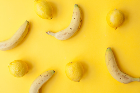 Peel banana and fruit and lemons on a yellow background an