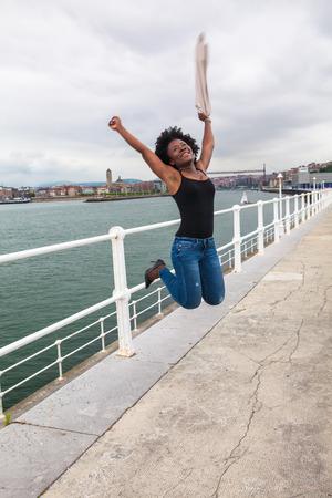 coastal city: Beautiful African woman jumping near a boardwalk in a coastal city in a cloudy day
