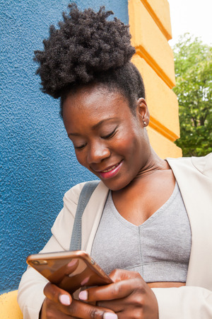 medium shot: Medium shot of an african young woman in sportswear looking at His mobile phone with a colorful blue and yellow wall