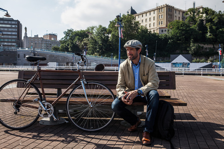 estilo urbano: Middle-aged man with Irish beret sitting on a bench With His urban bike a sunny day